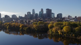 DX0001_002341 - 5.7K stock footage aerial video reverse view of skyline of Downtown Minneapolis, Minnesota, seen from river, reveal bridge