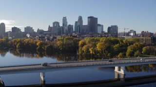 DX0001_002350 - 5.7K stock footage aerial video of flying by the bridge over river with a view of the skyline of Downtown Minneapolis, Minnesota