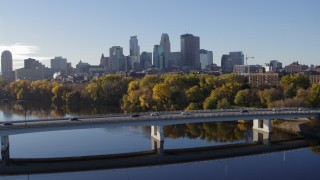 DX0001_002351 - 5.7K stock footage aerial video of passing by the bridge over river with a view of the skyline of Downtown Minneapolis, Minnesota