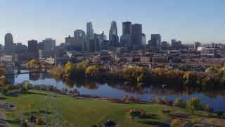 DX0001_002353 - 5.7K stock footage aerial video descend toward riverfront park with a view of the skyline of Downtown Minneapolis, Minnesota