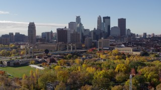 DX0001_002358 - 5.7K stock footage aerial video ascend from trees to flyby the city's skyline across the river, Downtown Minneapolis, Minnesota