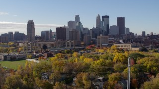 DX0001_002359 - 5.7K stock footage aerial video descend toward trees to flyby the city's skyline across the river, Downtown Minneapolis, Minnesota