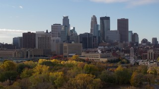 DX0001_002368 - 5.7K stock footage aerial video ascend from trees to reveal Mississippi River, focus on skyline of Downtown Minneapolis, Minnesota