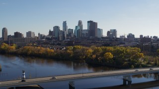 DX0001_002455 - 5.7K stock footage aerial video reverse view of the city skyline, reveal bridge spanning Mississippi River, Downtown Minneapolis, Minnesota