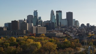 DX0001_002481 - 5.7K stock footage aerial video focus on the city skyline while flying by trees, Downtown Minneapolis, Minnesota