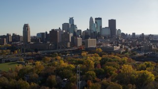 DX0001_002489 - 5.7K stock footage aerial video of flying by fall trees and the city skyline, Downtown Minneapolis, Minnesota