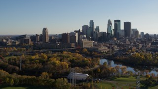 DX0001_002497 - 5.7K stock footage aerial video descend toward park with view of city skyline across the Mississippi River, Downtown Minneapolis, Minnesota