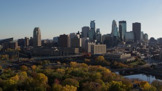 DX0001_002500 - 5.7K stock footage aerial video fly over trees with view of city skyline, reveal Mississippi River, Downtown Minneapolis, Minnesota