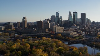 DX0001_002501 - 5.7K stock footage aerial video descend by trees with view of city skyline and Mississippi River, Downtown Minneapolis, Minnesota