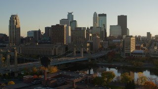 DX0001_002515 - 5.7K stock footage aerial video flying by Hennepin Avenue Bridge and city skyline at sunset, Downtown Minneapolis, Minnesota