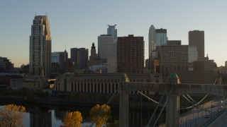 DX0001_002517 - 5.7K stock footage aerial video ascend by Hennepin Avenue Bridge, USPS and apartment buildings at sunset, Downtown Minneapolis, Minnesota