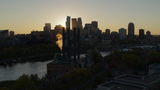 DX0001_002520 - 5.7K stock footage aerial video of the city skyline across the river while flying by a power plant at sunset, Downtown Minneapolis, Minnesota