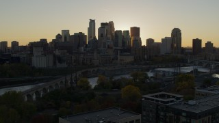 DX0001_002528 - 5.7K stock footage aerial video view of city skyline during descent by bridge and river at sunset, Downtown Minneapolis, Minnesota