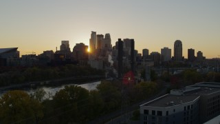 DX0001_002530 - 5.7K stock footage aerial video of city skyline while flying over power plant and river at sunset, Downtown Minneapolis, Minnesota
