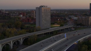 DX0001_002549 - 5.7K stock footage aerial video of reverse view of a condo complex beside a bridge at sunset, Minneapolis, Minnesota