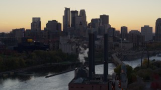 DX0001_002552 - 5.7K stock footage aerial video flyby power plant and river to focus on skyline at sunset, Downtown Minneapolis, Minnesota