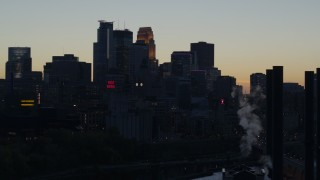 DX0001_002559 - 5.7K stock footage aerial video flyby smoke stacks with view of the city skyline at twilight, Downtown Minneapolis, Minnesota