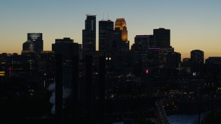 DX0001_002579 - 5.7K stock footage aerial video pass skyscrapers lit for night in the city skyline at twilight and ascend, Downtown Minneapolis, Minnesota