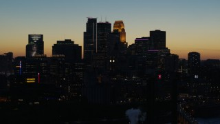 DX0001_002581 - 5.7K stock footage aerial video ascend by the city skyline lit for the night at twilight, Downtown Minneapolis, Minnesota