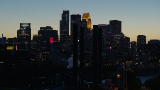 DX0001_002583 - 5.7K stock footage aerial video flyby smoke stacks and the city skyline lit for the night at twilight, Downtown Minneapolis, Minnesota