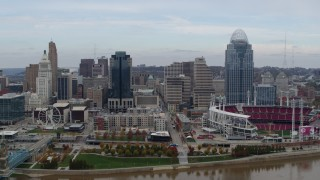 DX0001_002592 - 5.7K stock footage aerial video focus on city skyline and baseball stadium during ascent from river, Downtown Cincinnati, Ohio