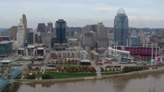 DX0001_002596 - 5.7K stock footage aerial video ascend and fly away from city skyline and baseball stadium by Ohio River, Downtown Cincinnati, Ohio