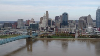DX0001_002600 - 5.7K stock footage aerial video flying by the city skyline and bridge spanning Ohio River, Downtown Cincinnati, Ohio