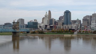 DX0001_002602 - 5.7K stock footage aerial video descend near bridge spanning Ohio River and focus on skyline of Downtown Cincinnati, Ohio