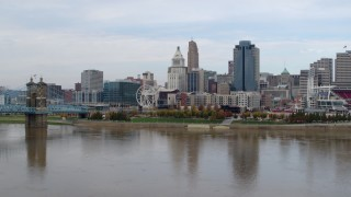 DX0001_002603 - 5.7K stock footage aerial video reverse view of skyline while flying low over Ohio River, Downtown Cincinnati, Ohio