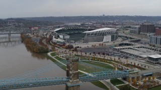 DX0001_002612 - 5.7K stock footage aerial video orbit football stadium before flying away from bridge, Downtown Cincinnati, Ohio