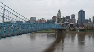 DX0001_002633 - 5.7K stock footage aerial video ascend from river beside the bridge with the city skyline in background, Downtown Cincinnati, Ohio