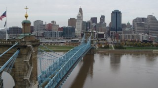 DX0001_002638 - 5.7K stock footage aerial video fly close to the Roebling Bridge spanning Ohio River near the city skyline, Downtown Cincinnati, Ohio