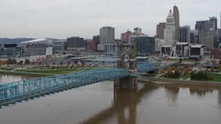 DX0001_002639 - 5.7K stock footage aerial video fly away from the Roebling Bridge spanning Ohio River near the city skyline, Downtown Cincinnati, Ohio