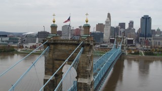 DX0001_002642 - 5.7K stock footage aerial video orbit flags on the Roebling Bridge spanning Ohio River, with view of the city skyline, Downtown Cincinnati, Ohio