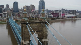 DX0001_002644 - 5.7K stock footage aerial video orbit flags on top of the Roebling Bridge, reveal the city skyline, Downtown Cincinnati, Ohio