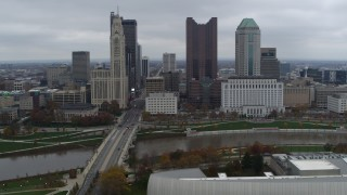 DX0001_002720 - 5.7K stock footage aerial video of flying by Discovery Bridge and Scioto River by city skyline, Downtown Columbus, Ohio