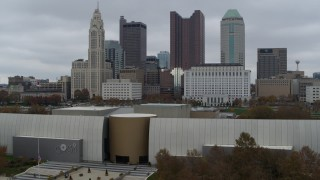 DX0001_002725 - 5.7K stock footage aerial video ascend over science museum to reveal river and approach city skyline, Downtown Columbus, Ohio