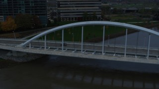 DX0001_002738 - 5.7K stock footage aerial video reverse view of the Main Street Bridge spanning the Scioto River at sunset, Downtown Columbus, Ohio