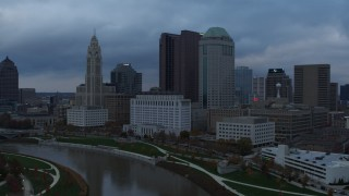 DX0001_002740 - 5.7K stock footage aerial video reverse view of city skyline on the other side of the Scioto River at sunset, Downtown Columbus, Ohio
