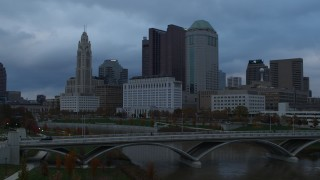 DX0001_002741 - 5.7K stock footage aerial video ascend over bridge for view of city skyline by the Scioto River at sunset, Downtown Columbus, Ohio