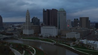 DX0001_002743 - 5.7K stock footage aerial video fly by and away from the city skyline by the Scioto River at sunset, Downtown Columbus, Ohio