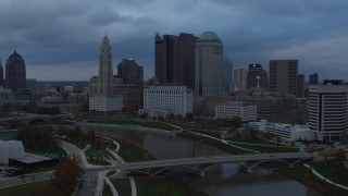 DX0001_002744 - 5.7K stock footage aerial video descend with view of bridge and city skyline by the Scioto River at sunset, Downtown Columbus, Ohio