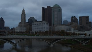 DX0001_002749 - 5.7K stock footage aerial video ascend from bridge for view of the city skyline and the Scioto River at sunset, Downtown Columbus, Ohio