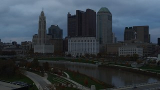 DX0001_002751 - 5.7K stock footage aerial video flying by the city skyline and the Scioto River at sunset, descend to reveal bridge, Downtown Columbus, Ohio