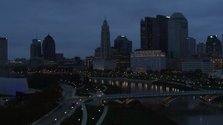 DX0001_002769 - 5.7K stock footage aerial video flying by the river and the city skyline at twilight to reveal a bridge in Downtown Columbus, Ohio