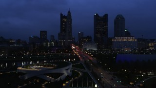 DX0001_002775 - 5.7K stock footage aerial video of passing by the city skyline across the bridge and river at twilight, Downtown Columbus, Ohio