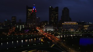 DX0001_002791 - 5.7K stock footage aerial video of passing a bridge spanning the river and city skyline at twilight, Downtown Columbus, Ohio