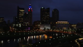 DX0001_002792 - 5.7K stock footage aerial video reverse view of a bridge spanning the river and city skyline at twilight during descent, Downtown Columbus, Ohio