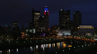 DX0001_002793 - 5.7K stock footage aerial video ascend to reveal the river and approach city skyline at night, Downtown Columbus, Ohio