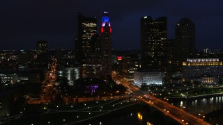 DX0001_002794 - 5.7K stock footage aerial video fly away from city skyline at night, reveal river, bridge and concert hall, Downtown Columbus, Ohio
